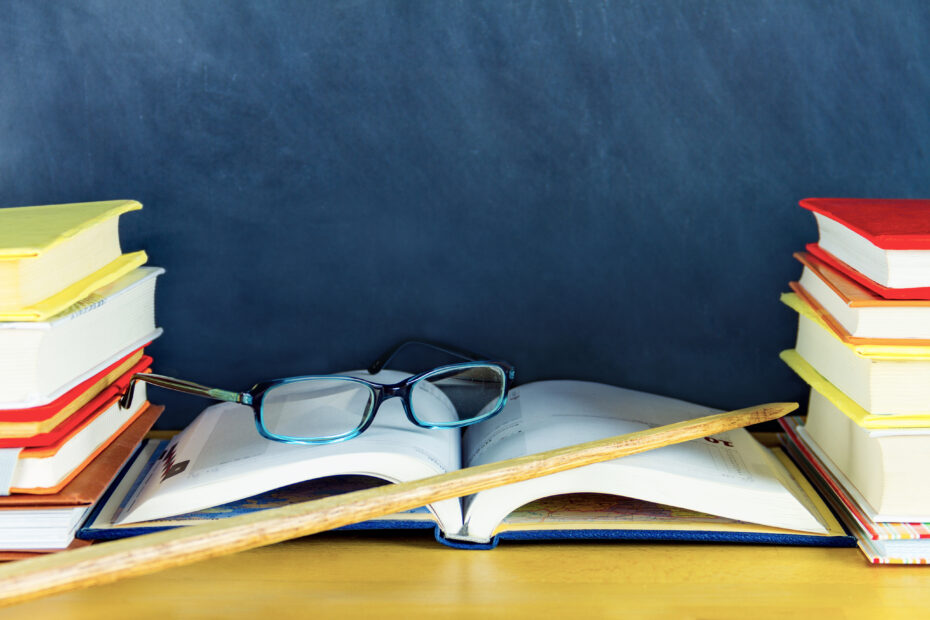Kirjoja, silmälasit ja karttakeppi.
