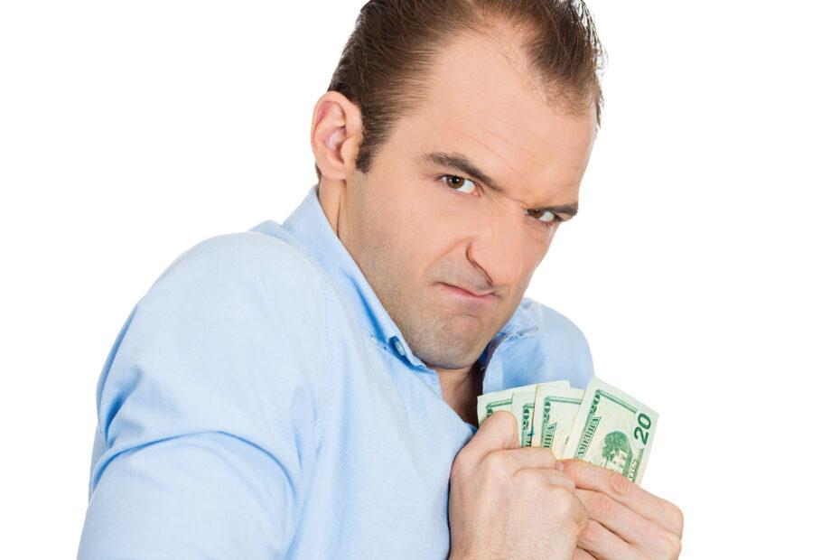 Ahne mies pitelee käsissään seteleitä.