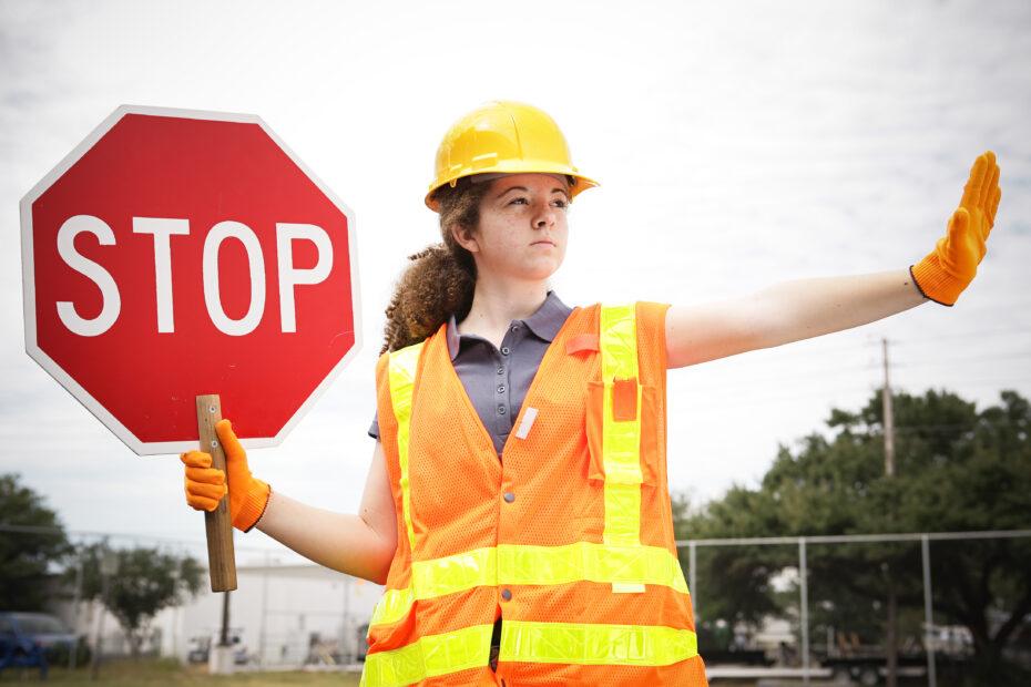 Huomioliiviin pukeutunut nainen pitelee stop-merkkiä.