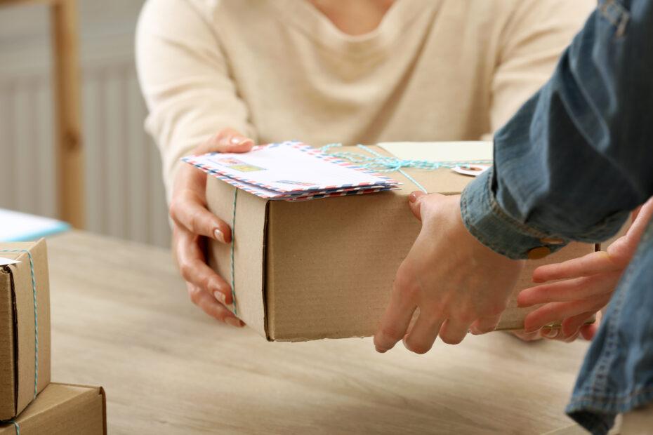 Asiakas ojentaa paketin postivirkailijalle.