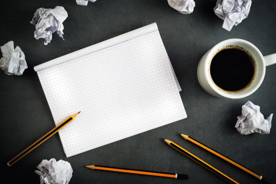 Kahvikuppi, tyhjä paperi ja paljon rypistettyjä papereita. Kirjoittajan blokki!