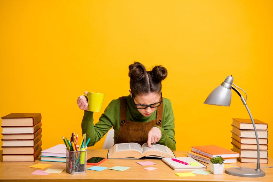 Opiskelija etsii kirjoista tietoa graduun.